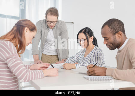 multiethnic middle aged business people working with papers together - Stock Photo