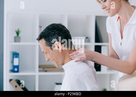 side view of masseuse doing seated neck massage for client at office - Stock Photo
