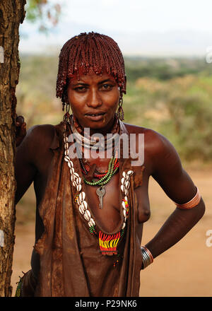 TURMI, OMO VALLEY, ETHIOPIA - 29 JULY 2013: Portrait of the woman from Hamer people resting under the tree in transit to the local marketplace in Omo  - Stock Photo