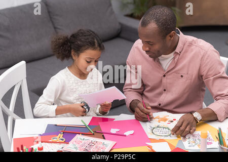 african american daughter cutting paper for greeting card on mothers day - Stock Photo