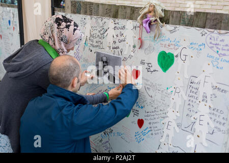 London, UK. 14th Jun, 2018.  Relatives of a father killed in the Grenfell fire on the first anniversary of the tower block disaster. 72 people died when the tower block in the borough of Kensington & Chelsea were killed in what has been called the largest fire since WW2. The 24-storey Grenfell Tower block of public housing flats in North Kensington, West London, United Kingdom. It caused 72 deaths, out of the 293 people in the building, including 2 who escaped and died in hospital. Over 70 were injured and left traumatised. Credit: RichardBaker/Alamy Live News - Stock Photo