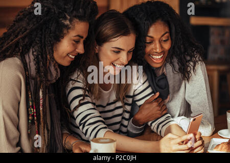 Three women sitting in a restaurant looking at mobile phone and laughing. Friends sitting at a cafe with coffee and snacks on the table looking at a m - Stock Photo