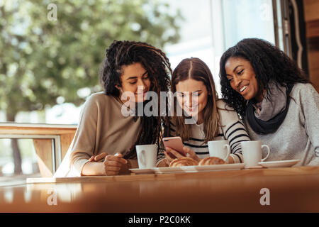 Three women sitting in a restaurant looking at mobile phone and smiling. Friends sitting at a cafe with coffee and snacks on the table looking at a mo - Stock Photo