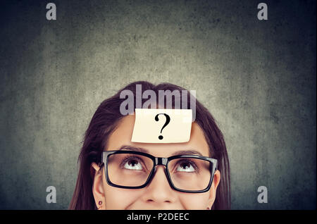 Young woman wearing black glasses with question mark on forehead looking up. - Stock Photo