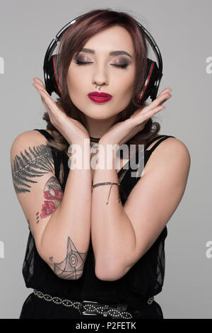 Young woman with tattoos wearing big headphones making a kissing face with her eyes closed - Stock Photo
