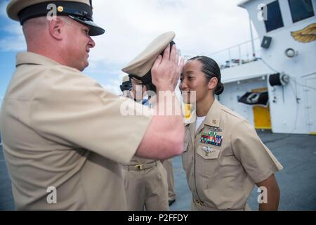 160916-M-TM809-819 PACIFIC OCEAN (Sept. 16, 2016) Chief Aviation Electrician's Mate Sean Almond, from New Harmony, Indiana, places a cover on Chief Hospital Corpsman Claudette Arenas, from Las Vegas, during the chief pinning ceremony on the flight deck of hospital ship USNS Mercy (T-AH 19). Four hospital corpsman attached to Mercy were promoted to the rank of chief petty officer. Deployed in support of Pacific Partnership 2016, Mercy is sailing to her homeport of San Diego. (U.S. Marine Corps photo by Sgt. Brittney Vella/Released) - Stock Photo