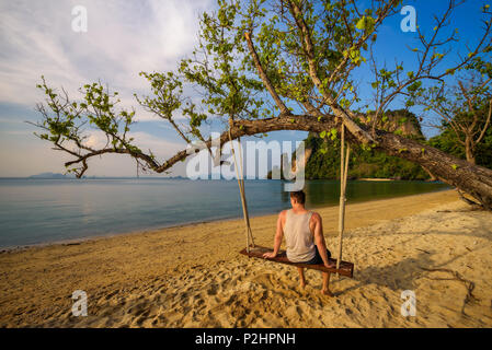 Young boy sits on a swing on Ko Hong island in Thailand - Stock Photo
