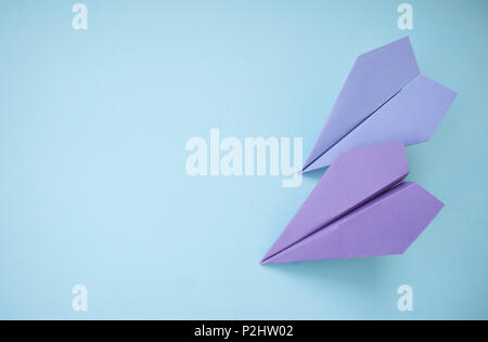 Flat lay of two purple paper planes on pastel blue background with text space. - Stock Photo