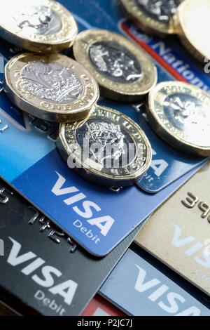 Visa Debit and Credit Cards with new Pound Coins - Stock Photo