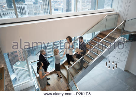 Business people handshaking on modern, urban office staircase - Stock Photo