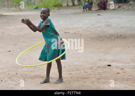 A girl uses a hula hoop in the Loreto Primary School in Rumbek, South Sudan. - Stock Photo