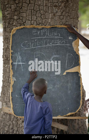 A boy points to letters on a blackboard in the Loreto Primary School in Rumbek, South Sudan. - Stock Photo