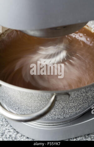 Mixer blending chocolate cake mix with motion blur on kitchen top - Stock Photo