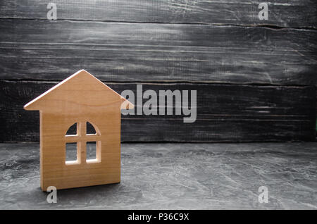 Wooden house on a gray concrete background. Concept of buying and selling housing, building a house. Rent of apartments. Realtors. Real estate, privat - Stock Photo