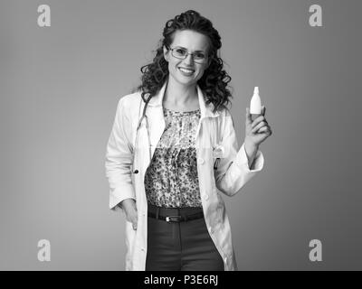 smiling pediatrist woman in white medical robe showing nasal drops isolated on background - Stock Photo