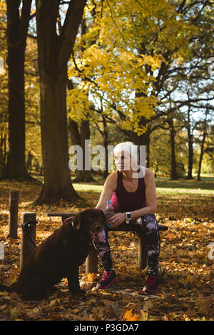 Thoughtful senior woman in a park with her dog - Stock Photo