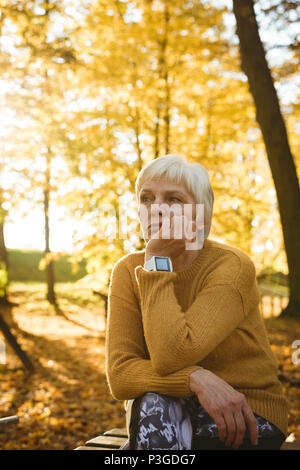 Thoughtful senior woman sitting in a park - Stock Photo