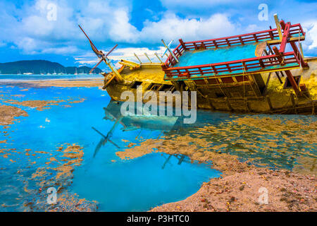 the old ship wreck stuck on the mud near Chalong gulf - Stock Photo