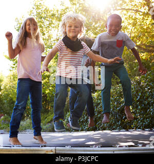 Four kids having fun together on a trampoline in the garden - Stock Photo