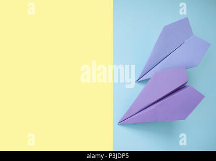 Flat lay of two paper planes on pastel yellow and blue background with text space. - Stock Photo