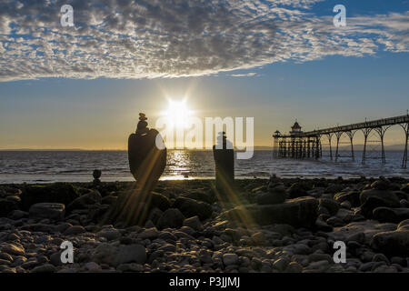 Stone sculptures on the beach with Clevedon pier in the background. - Stock Photo