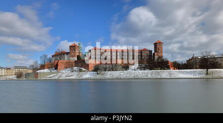 Picturesque view at castle in Krakow, Poland, from opposite Vistula river bank, winter, beautiful white clouds on sky, little snow, long exposure - Stock Photo