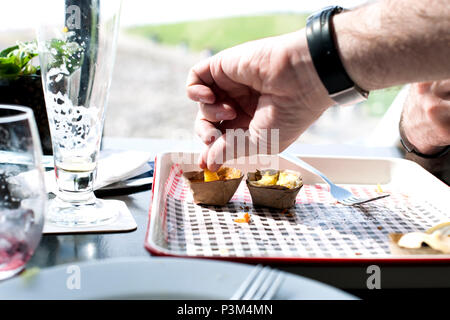 the man is eating fast food in a cafe. A table by the window. Empty dirty dish. - Stock Photo