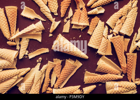 Crushed ice cream waffle cones on dark brown background, flat lay - Stock Photo