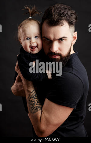 Handsome tattooed young man holding cute little baby on black background - Stock Photo
