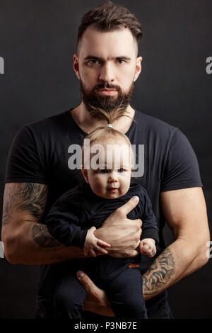 Handsome tattooed beared man holding cute little baby on black background - Stock Photo