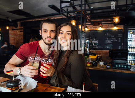 Positive young loving couple meeting in a cafe. - Stock Photo