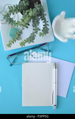 Turquoise blue top view flat layout styled desktop with blank notebook and car for copy. Working from home office. Invitation, diary or greeting card. - Stock Photo