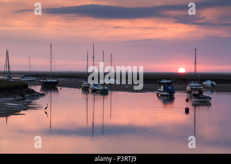 The sun rising behind sailing boats in the harbour at Wells next the Sea with a heron in the foreground. - Stock Photo