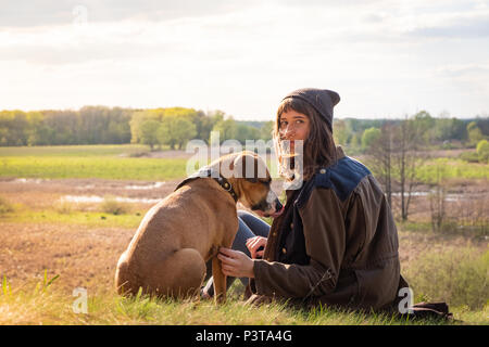 Beautiful hiking girl sit on hill with pet dog at walk. Young female person together with staffordshire terrier at meadow on warm sunny afternoon - Stock Photo