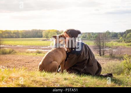 Beautiful hiking girl sit on hill and kiss pet dog at walk. Young female person together with staffordshire terrier at meadow on warm sunny afternoon - Stock Photo
