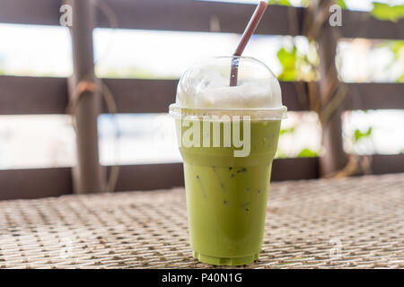 Iced green tea with milk in the plastic cup on the metal table against white background - Stock Photo