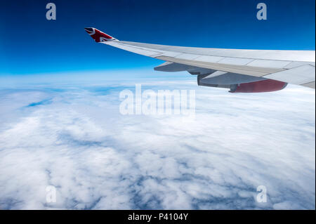 view from airplane window of the aircraft wing and engine with cloudscape - Stock Photo