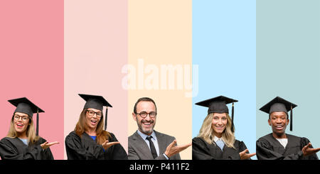 Senior teacher with his graduate students holding something in empty hand - Stock Photo