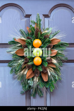 Christmas pine wreath decoration made of 2 oranges & a green apple, set off by pine needles & cones. Colonial Williamsburg annual competition display. - Stock Photo