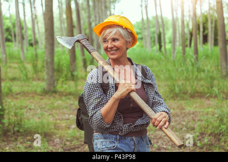 experienced female lumberjack while visiting a forest before cutting some trees - Stock Photo