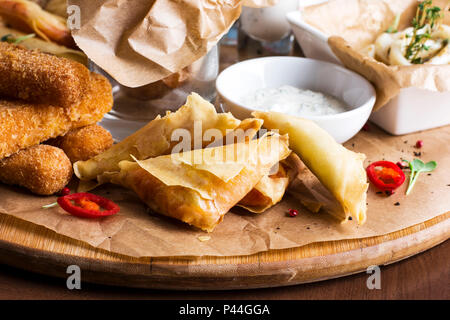 Cheese sticks in batter, spicy envelopes with sauce on round wooden Board - Stock Photo