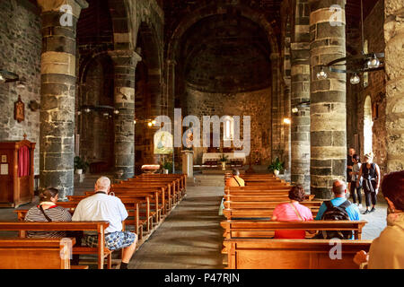 Tourists sitting quietly inside historic  St Margaret of Antioch Church, Vernazza, Cinque Terre, Italy - Stock Photo