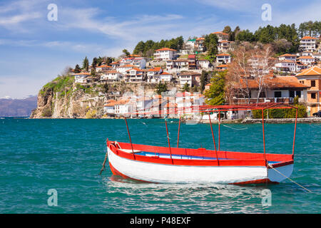 Ohrid, Republic of Macedonia : Boat moored on the Ohrid Lake with general view of the Unesco listed old town in background. - Stock Photo