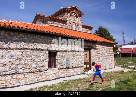 Ohrid, Republic of Macedonia : A child in an Spiderman costume walks past the Holy Mother of God Peribleptos church (1295) one of the oldest churches  - Stock Photo