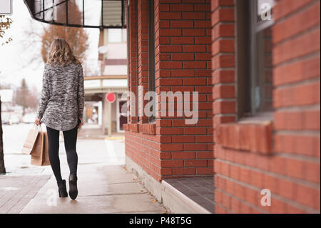 Rear view of woman with shopping bag walking in passage - Stock Photo