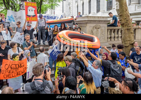 A massive public protest was organized in New York City in observance of World Refugee Day. Hundreds of New Yorkers from dozens of refugee, immigrant, religious, and community organizations staged a march from Bryant Park and rally in front of the United Nations. Protesters called attention to the delicate issues by representing refugees excluded by Trump administration with life-size orange rafts symbolizing refugee ocean crossings, large-scale photos of refugees, and by reading of the names of refugees who have died in transit. (Photo by Erik McGregor/Pacific Press) - Stock Photo