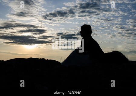 Silhouette of young woman sitting on top of rocks of Pedras Negras or Pundo Andongo during sunset with dramatic sky, Angola, Africa. - Stock Photo