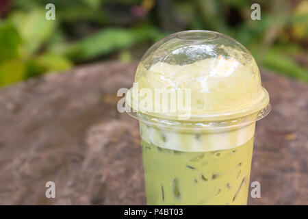 Green tea iced frappe in takeaway cup on wood table background. - Stock Photo