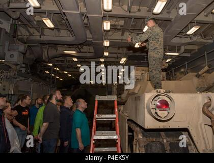 180616-N-PC620-0050  KIEL, Germany (June 16, 2018) U.S. Marine Cpl. Jonathan Klein, from San Antonio, gives a tour of an M1A1 Abrams tank, attached to the 26th Marine Expeditionary Unit, aboard the Harpers Ferry-class dock landing ship USS Oak Hill (LSD 51), in Kiel, Germany, during Kiel Week 2018, June 16. Oak Hill, home-ported in Virginia Beach, Virginia, is conducting naval operations in the U.S. 6th Fleet area of operations. (U.S. Navy photo by Mass Communication Specialist 3rd Class Michael H. Lehman/Released) - Stock Photo