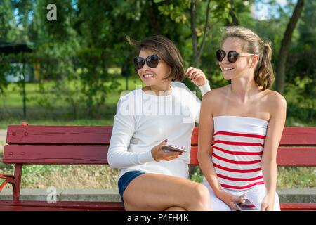 Mother and daughter teenager looking to the side, sitting on a bench in the park. Communication between parent and child. Copy space - Stock Photo